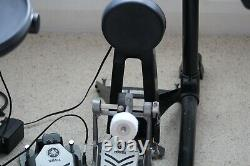 Yamaha electronic drum kit with rolled headphones, amplifier, and a music stand